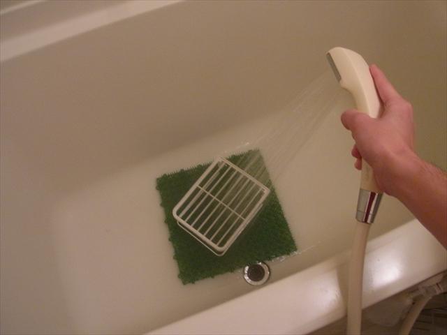 人工芝と棚をお湯で洗う